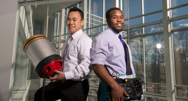 """Students Viet Tran (L) and Seth Robertson with their invention, a sound extinguisher, at the Fairfax Campus. Photo by Alexis Glenn/Creative Services/George Mason University"""